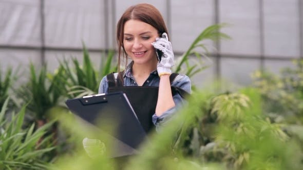Thumbnail for Female Gardener Talking On The Phone In Greenhouse