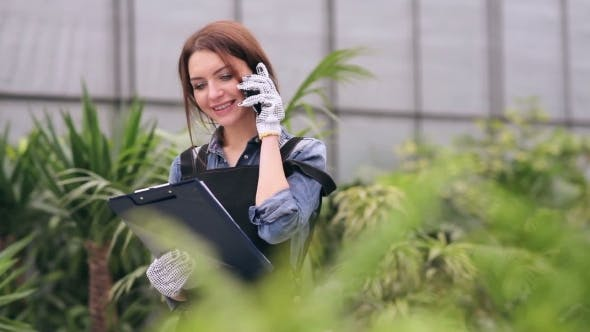 Thumbnail for Florist Talking On The Phone In Greenhouse