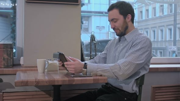 Thumbnail for Yawns Young Man Using Tablet Computer In Cafe