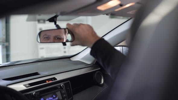 Cover Image for Young Businessman In Suit Sitting In The Car And Looking In The Front View Mirror.