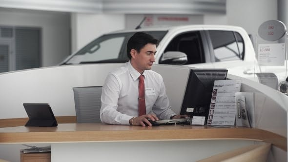 Thumbnail for Car Salesman Sitting In Showroom