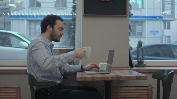 Thumbnail for Successful Young Businessman Is Working On His Laptop In Cafe And Drinking Coffee