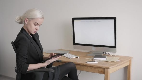 Thumbnail for Young Woman Using Tablet PC At Her Workplace