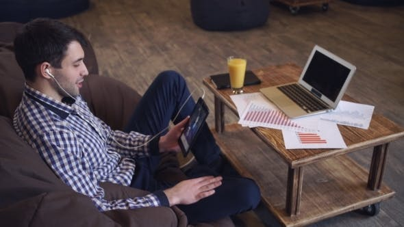 Thumbnail for Attractive Man Holding Tablet In Hand, Headphones Dressed, Online Conference.