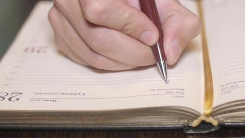 Right Man's Hand Write Word Buisness On Paper Notebook By a Pen.