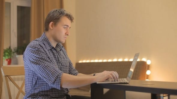 Young Man Working At a Laptop At Home