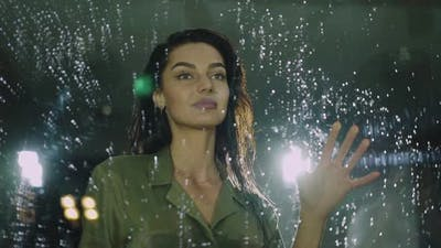 Beautiful Woman Touches the Glass Door with Rain Drops and Smiling