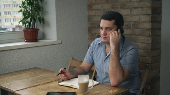 Thumbnail for Attractive Adult Man Resting In a Cafe And Talks On The Phone.
