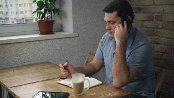 Thumbnail for Manager Sitting In Cafe, Talking On Phone, Taking Notes On a Pad.
