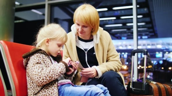 Cover Image for Girl 5-6 Years, Use Your Phone In The Airport Terminal, Next To Her Mother Sitting