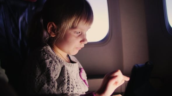 Thumbnail for Little Girl Playing With The Tablet On The Aircraft