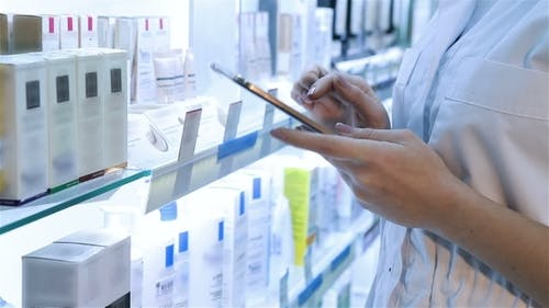 Hands With The Tablet On The Background Of Pharmacy