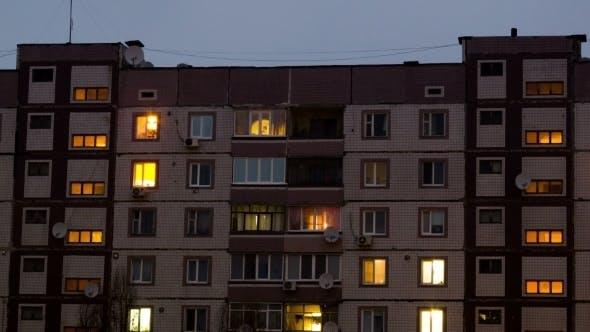 Thumbnail for Mehrgeschossiges Gebäude mit wechselnder Fensterbeleuchtung bei Nacht.