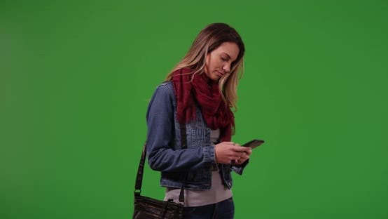 Thumbnail for Trendy millennial girl messaging on smartphone on green screen