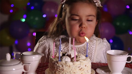 Little Girl Blowing Out The Candles of Birthday Cake