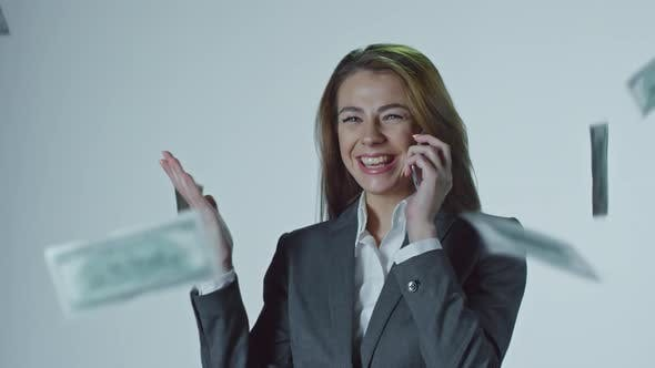 Thumbnail for Money Falling on Businesswoman Talking on Mobile Phone