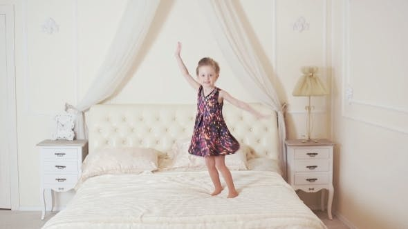 Thumbnail for Happy Girl Jumping And Dancing On The Bed