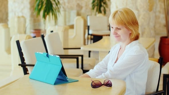 Cover Image for Attractive Woman Has a Video Chat Over The Tablet