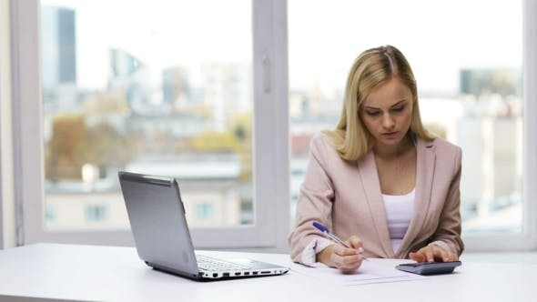 Thumbnail for Businesswoman With Laptop, Calculator And Papers