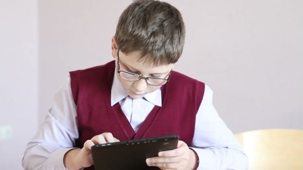 Thumbnail for Boy With Glasses Playing The Tablet At School