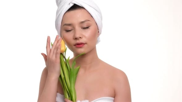 Thumbnail for Beautiful Girl With a Towel On Head Holding Yellow Tulips