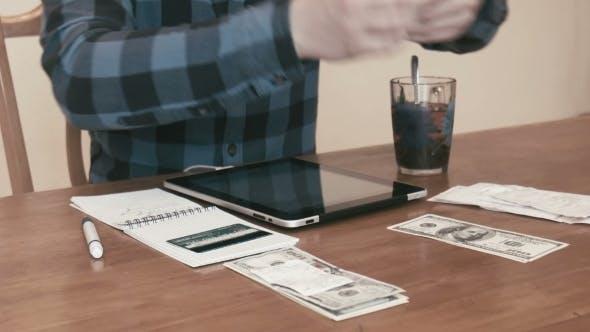 The Male Considers Bills Using Digital Tablet