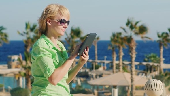 Thumbnail for A Female Tourist Enjoys The Tablet In a Recreation Area
