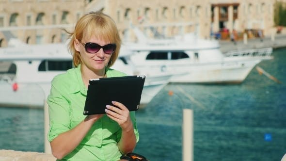 Cover Image for A Female Tourist Enjoys The Tablet Against The Backdrop Of The Bay With Yachts
