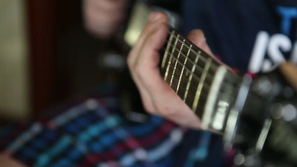 Thumbnail for Man Plays Guitar, His Fingers On The Fretboard