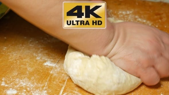 Thumbnail for Baker Kneading Dough With Hand On Table In Flour