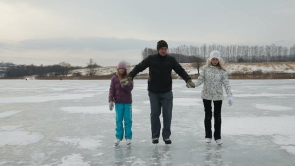 Thumbnail for Father With Daughters Ice Skating On Frozen Lake