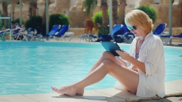 Thumbnail for Woman Relaxing By The Pool, Enjoying The Tablet