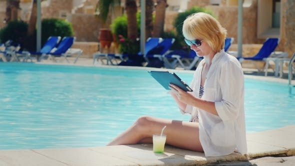 Cover Image for Woman Relaxing By The Pool, Enjoy a Tablet, Drink a Cocktail
