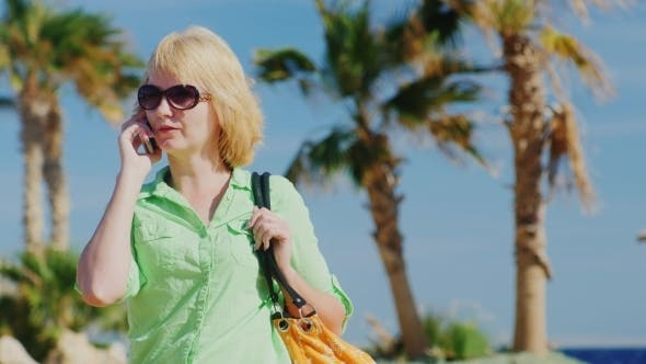 Cover Image for Woman Tourist In Sunglasses Talking On The Phone On The Background Of Sky And Palm Trees