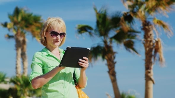 Cover Image for A Woman In a Light Green Shirt Using Tablet Against The Sky And Palm Trees