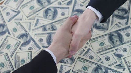 Business Handshake on the Background of Dollars