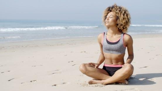 Thumbnail for Frau sitzt auf dem Strand in Lotus Pose