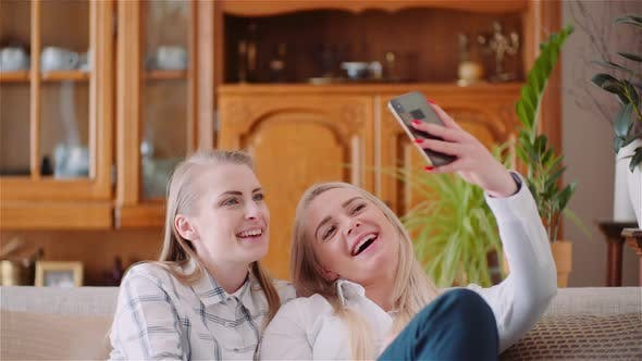 Two Positive Energetic Women Taking Selfie Photo on a Sofa in Luxury Modern Living Room