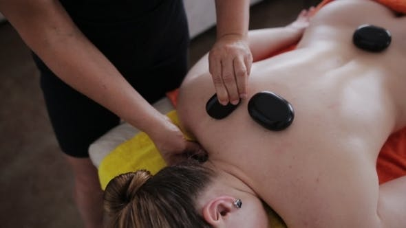 Thumbnail for Masseuse Using Hot Stone Massage Therapy On a Beautiful Aucasian Client