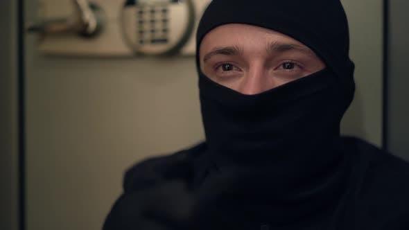 Thumbnail for Porträt von jungen kaukasischen Dieb in schwarzer Kleidung und Sturmhaube reiben seine Hände. Der Kerl stehlen
