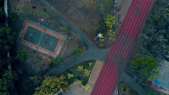 Running Track By Playground Between Forest and Court