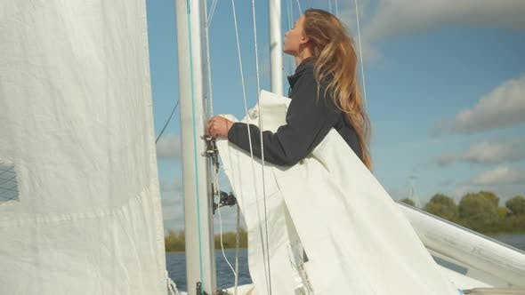 A Beautiful Young Sportswoman Studies the Rigging and Rigging of a Sports Yacht. Learning To Raise a