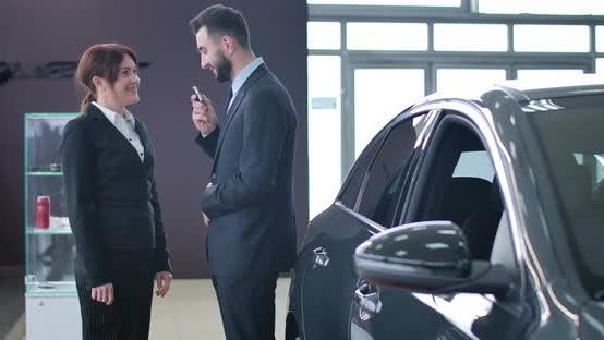 Thumbnail for Positive Handsome Male Trader Giving Car Keys To Smiling Successful Female Client