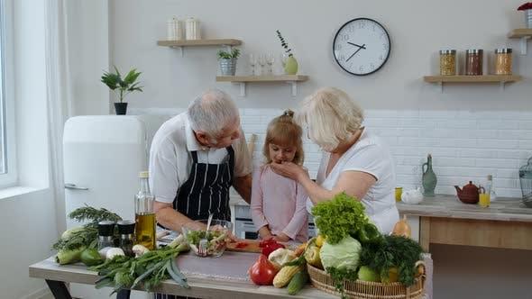 Thumbnail for Elderly Grandparents in Kitchen Feeding Grandchild Girl with Chopped Red Pepper. Vegetarian Diet