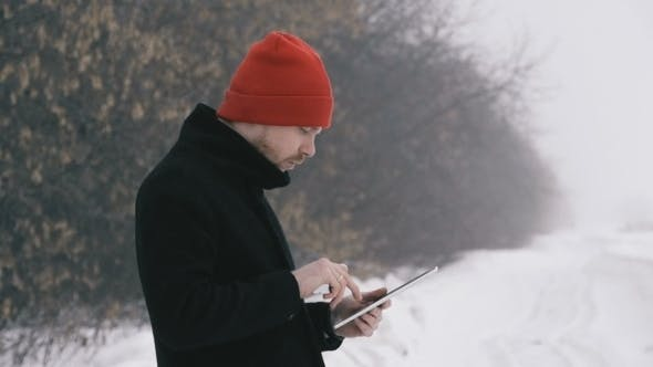 Thumbnail for Man Smokes An Electronic Cigarette And Use Tablet In The Park