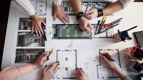 Thumbnail for Four Architects Discussing Plan Together At Desk Timalaps