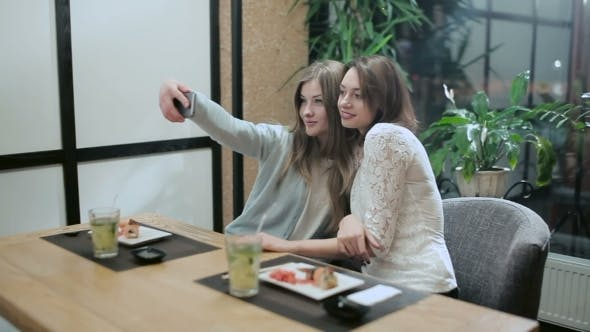Cover Image for Two Girls Taking Selfies In Japanese Restaurant
