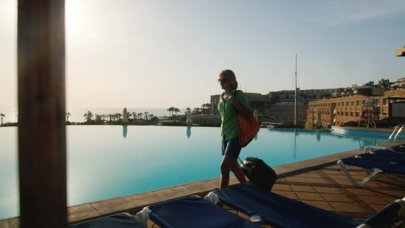 Cover Image for Woman With Travel Bag Walking On Recreation Area Along The Pool