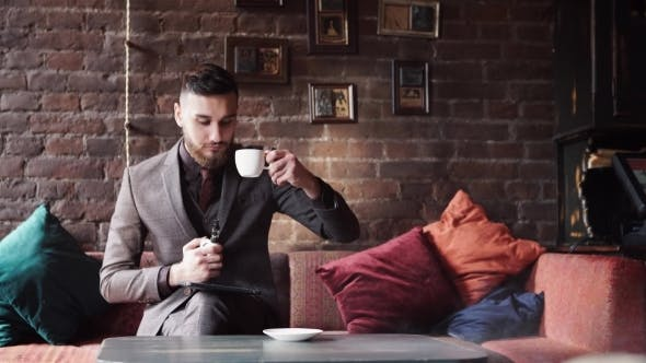 Thumbnail for Man Using an Advanced Personal E-cigarette and Drink Coffee