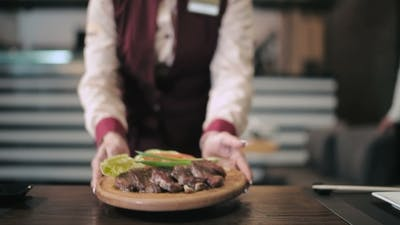 Waiter Serves Customers In Restaurant.
